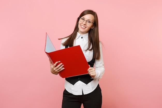 분홍색 배경에 격리된 서류 문서를 위한 빨간색 폴더를 들고 안경을 쓴 젊고 성공적인 브루네트 비즈니스 여성. 여사장님. 성취 경력 부입니다. 광고 공간을 복사합니다.