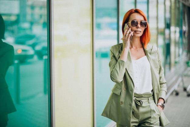 전화 통화하는 녹색 소송에서 젊은 아름 다운 성공적인 여자
