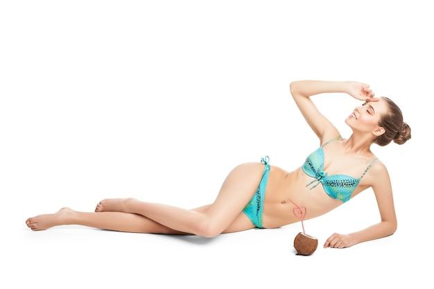 ストローから新鮮なココナッツジュースを飲む若い美しい夏の女の子