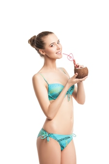 Young beautiful  summer girl drinking fresh coconut juice from a straw