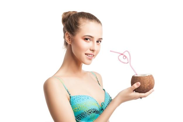 ストローで新鮮なココナッツを保持している若い美しい夏の女の子