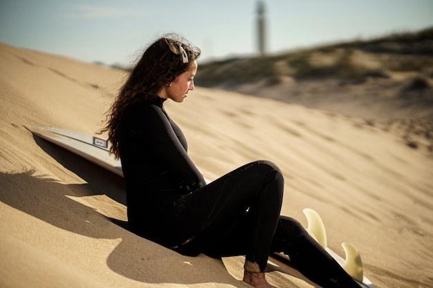 해질녘 해변에서 젊은 아름다운 서퍼 여성