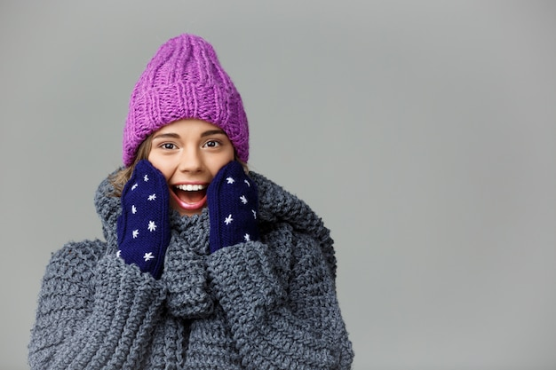 Young beautiful surprised fair-haired woman in knited hat sweater and mittens smiling on grey.