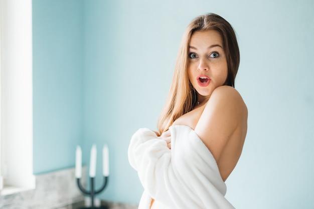 シャワーで彼女の体を覆う若い美しい驚きの女性
