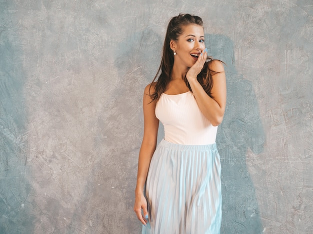 Young beautiful surprised woman looking  with hands near face. trendy girl in casual summer clothes. female posing near gray wall