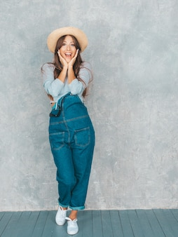 Young beautiful surprised woman looking   with hands near face. trendy girl in casual summer overalls clothes and hat. female posing near gray wall in studio