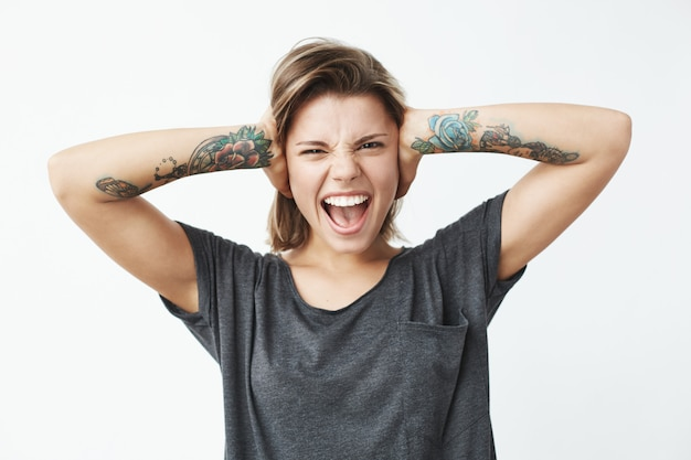 Young beautiful tattooed girl closing ears with hands shouting .