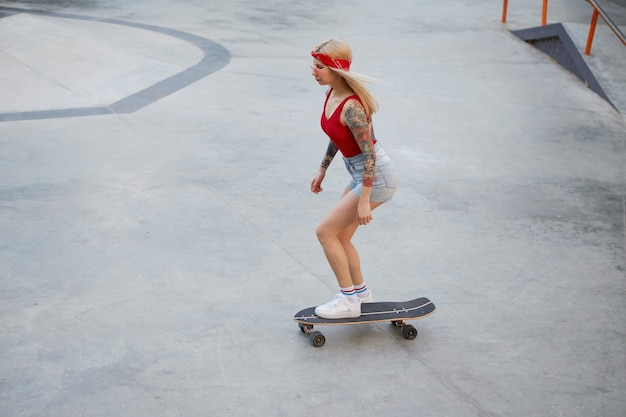 Young beautiful tattooed lady with blonde hair in a red t-shirt and denim shorts, with a knitted bandana on her head, enjoying the day and raiding on skateboard in skate park.