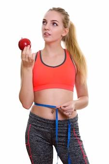 赤いリンゴを保持している若い美しい10代の少女