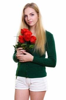 赤いバラを保持している若い美しい10代の少女