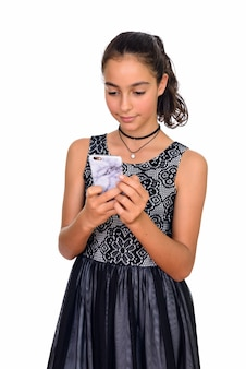 Young beautiful teenage girl using mobile phone isolated against white space