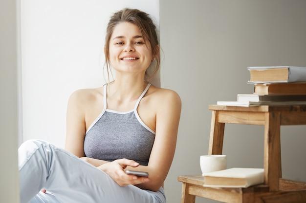 Giovane bella donna adolescente navigare in internet al telefono sorridente seduta sul pavimento tra i vecchi libri vicino alla finestra sul muro bianco.