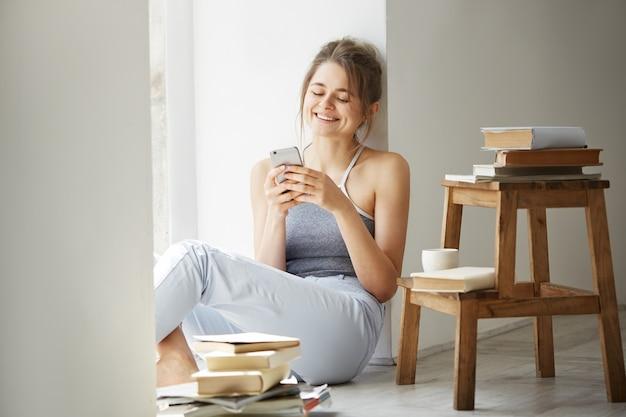 Web surf praticante della giovane bella donna adolescente che esamina seduta sorridente dello schermo del telefono sul pavimento fra i vecchi libri vicino alla finestra sopra la parete bianca.