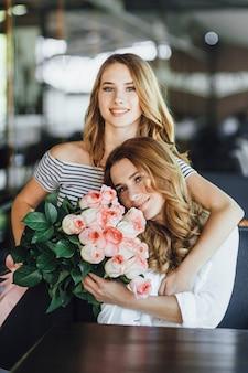 Молодая красивая дочка-подросток дарит маме букет роз на летней террасе кафе