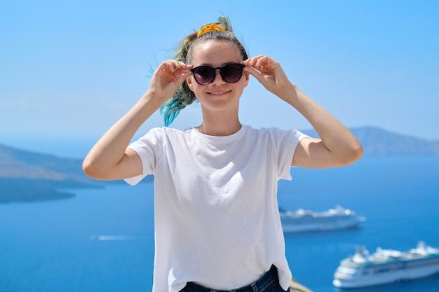 笑顔でポーズをとる若い美しいティーンエイジャーの女の子の観光客、有名なギリシャの島サントリーニ島のエーゲ海の白いクルーズライナーと背景の夏の日当たりの良い風光明媚な海の風景