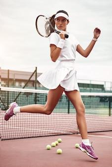 코트에 라켓을 들고 젊고 아름다운 테니스 선수
