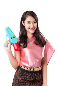 タイのソンクラン祭り、白で隔離される水鉄砲を保持している伝統衣装の若い美しいタイの女性。