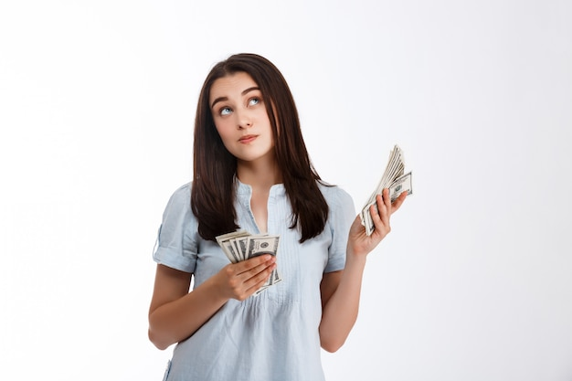 Young beautiful thoughtfully looking up business girl holding money over white wall