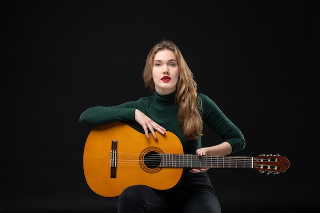 Young beautiful tired musician girl holding guitar on dark
