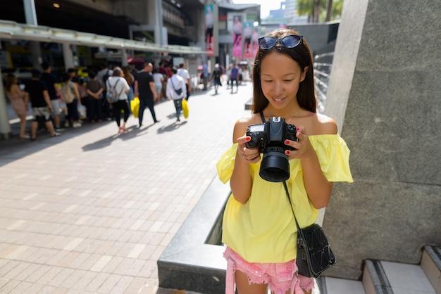 バンコクの街を探索する若い美しい観光女性