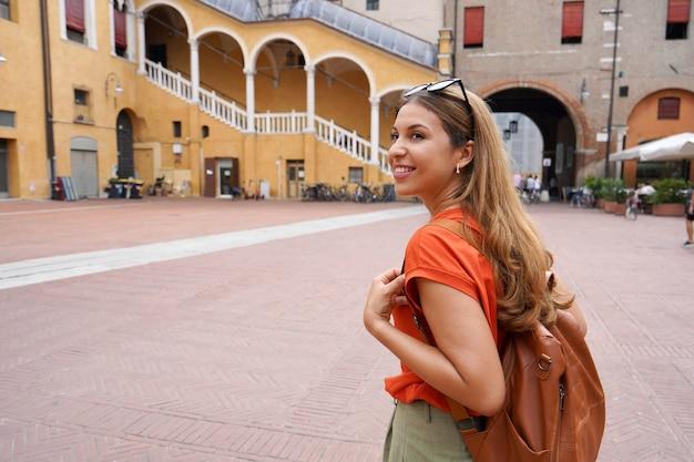 Young beautiful tourist woman visiting piazza del municipio square in ferrara, italy