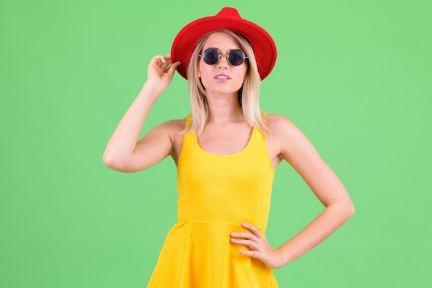Young beautiful tourist woman with blond hair on chroma key on green