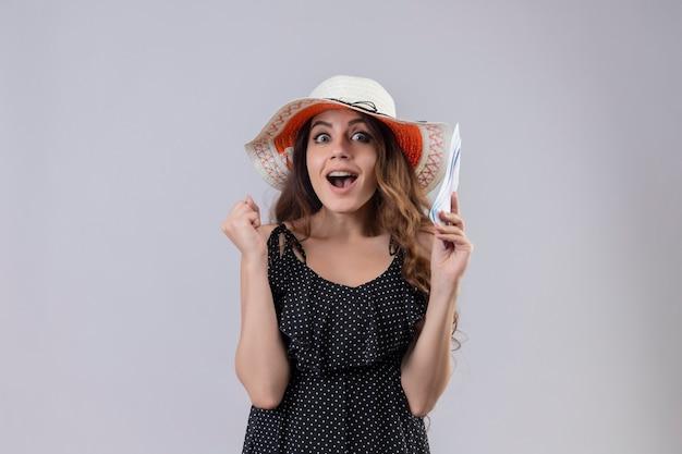 Ragazza giovane bella viaggiatrice in vestito a pois in cappello estivo in possesso di biglietti aerei cercando uscito e felice alzando il pugno gioendo del suo successo e vittoria in piedi su sfondo bianco