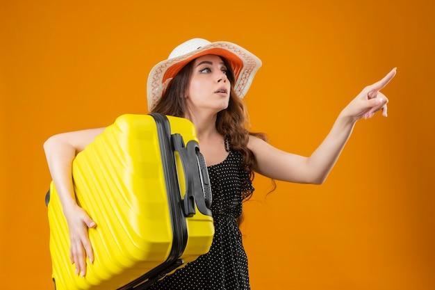 Giovane bella ragazza del viaggiatore in vestito a pois in cappello estivo che tiene la valigia che osserva da parte che indica con il dito a qualcosa di intrigato in piedi su sfondo giallo