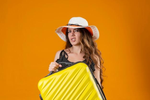Ragazza giovane bella viaggiatore in vestito a pois in cappello estivo che tiene la valigia che guarda l'obbiettivo con espressione scettica in piedi su sfondo giallo