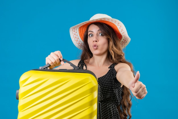 Ragazza giovane bella viaggiatore in vestito a pois in cappello estivo che tiene la valigia guardando uscito e felice che mostra i pollici in su gioendo del suo successo e vittoria in piedi su sfondo blu