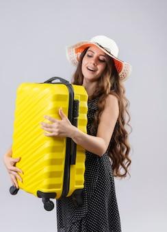 Ragazza giovane bella viaggiatore in vestito a pois in cappello estivo che tiene la valigia guardandolo con un sorriso felice sul viso in piedi su sfondo bianco