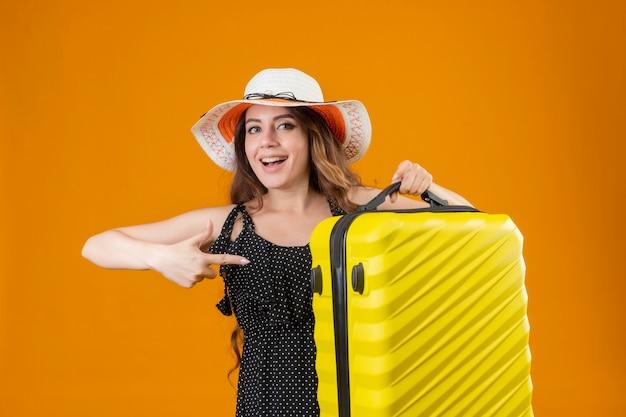 Giovane bella ragazza di viaggiatori in abito a pois in cappello estivo tenendo la valigia puntando con il dito verso di essa guardando la telecamera sorridendo allegramente felice e positivo in piedi su backgr arancione