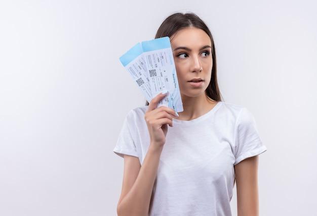Giovane bella ragazza del viaggiatore che tiene i biglietti aerei che osserva da parte confusa e molto ansiosa