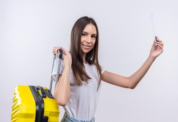 スーツケースと航空券を持って幸せで前向きな笑顔の若い美しい旅行者の女の子