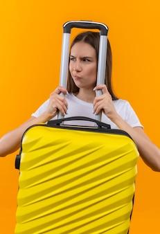 Giovane bella ragazza del viaggiatore che tiene la valigia che osserva da parte scontento