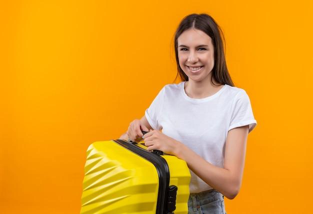 スーツケースを持って元気に笑顔でポジティブで幸せな若い美しい旅行者の女の子