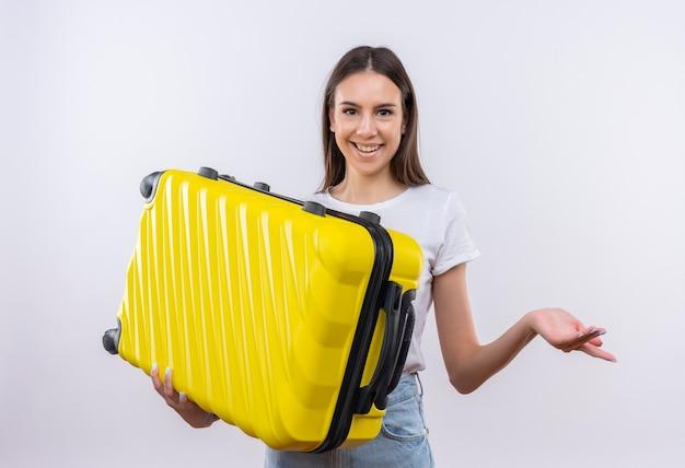 Молодая красивая путешественница девушка держит чемодан позитивно и счастливо улыбается