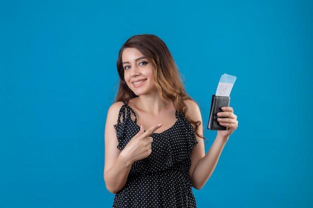 Молодая красивая девушка-путешественница в платье в горошек, держащая авиабилеты, смотрит в камеру, счастливая и позитивная улыбка, весело указывая пальцем на билеты, стоящие на синем фоне