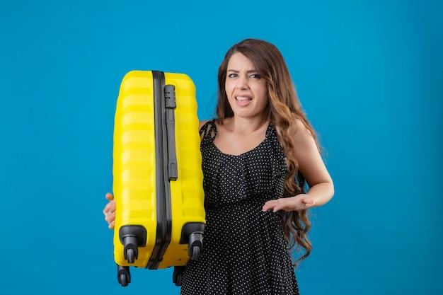 青い背景の上に立っている顔に嫌な表情で不機嫌そうな探しているスーツケースを持って水玉のドレスの若い美しい旅行者の女の子