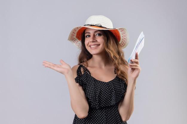 Молодая красивая девушка путешественника в платье в горошек в летней шляпе держит авиабилеты, весело улыбаясь, представляя руку ее руки, стоящую на белом фоне