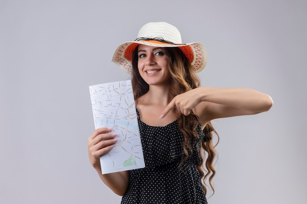 白い背景の上に元気に立って笑ってそれに指で指しているマップを保持している夏帽子の水玉のドレスの若い美しい旅行者の女の子