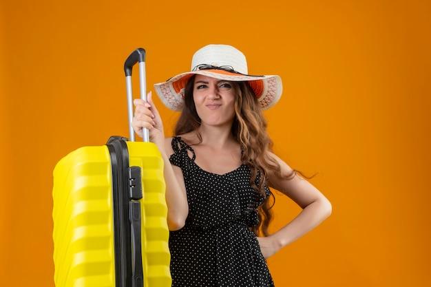 Молодая красивая девушка-путешественница в платье в горошек в летней шляпе с чемоданом разочарована, стоя на желтом фоне