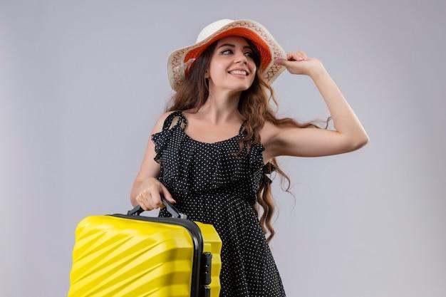 Молодая красивая девушка путешественника в платье в горошек в летней шляпе держит чемодан, глядя в сторону, весело улыбаясь и позитивно стоя на белом фоне