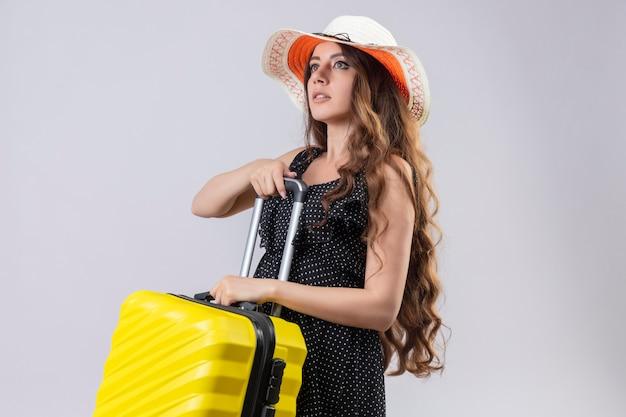 白い背景の上に立っている自信を持って真剣な表情で離れて見てスーツケースを持って夏帽子の水玉のドレスの若い美しい旅行者の女の子
