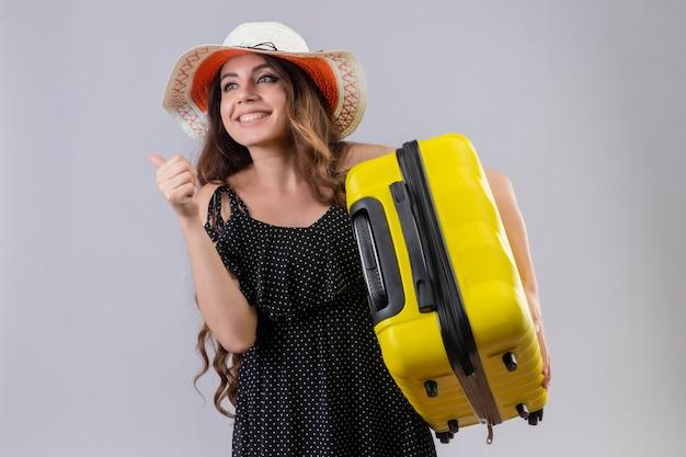 彼女の成功と勝利の白い背景の上に立って喜んで親指を出て、幸せな親指を現してスーツケースを持って夏帽子の水玉のドレスの若い美しい旅行者の女の子