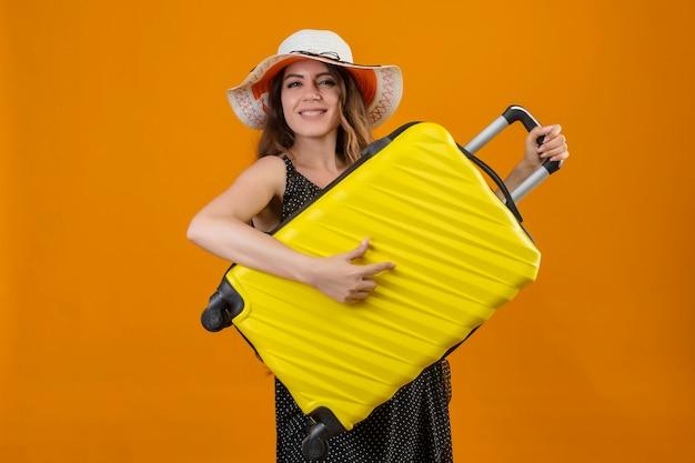 Молодая красивая девушка путешественника в платье в горошек в летней шляпе держит чемодан, используя в качестве гитары, веселится, радостно и счастливо стоя на желтом фоне