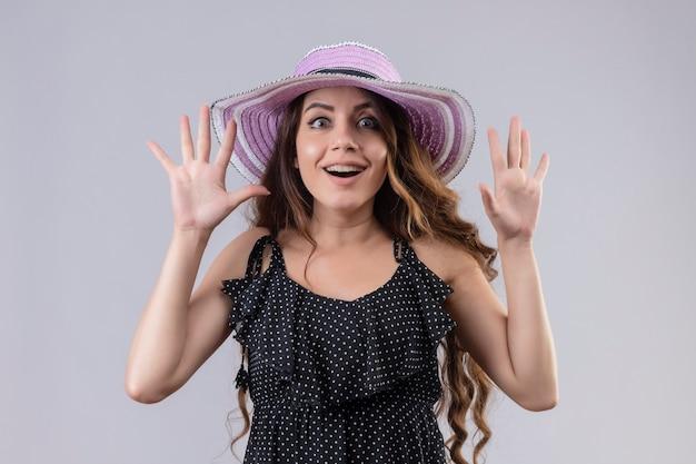 降伏で上げられた手で夏帽子立っている水玉のドレスの若い美しい旅行者の女の子は驚いて、白い背景に驚いた