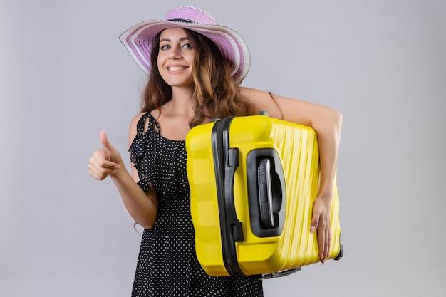 白い背景の上に立って親指を元気に見せて元気に笑顔でカメラを見てスーツケースを持って夏帽子の若い美しい旅行者の女の子