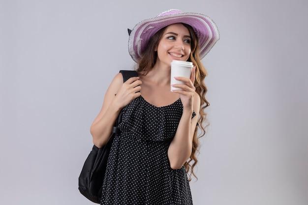 Молодая красивая девушка путешественника в летней шляпе с рюкзаком, держа чашку кофе, весело улыбаясь и позитивно глядя в сторону, стоя на белом фоне