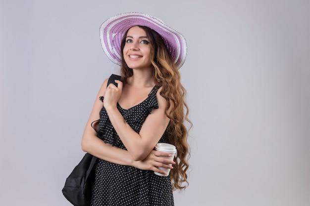 Молодая красивая девушка путешественника в летней шляпе с рюкзаком, держащая чашку кофе, весело улыбаясь, счастливая и позитивная, стоя на белом фоне